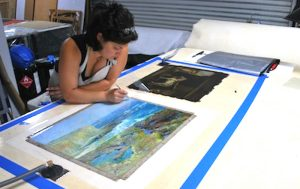 Oriana Montemurro, Art Conservator, working on the hot table lining a painting.